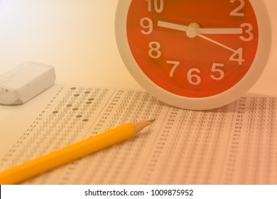 Answers sheet with yellow sharp pencil, clock and rubber selective focus, blur background. Take the exam timely concept.