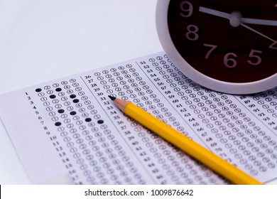 Answers sheet with yellow sharp pencil, clock isolated on white background, selective focus, blur background. Take the exam timely concept.