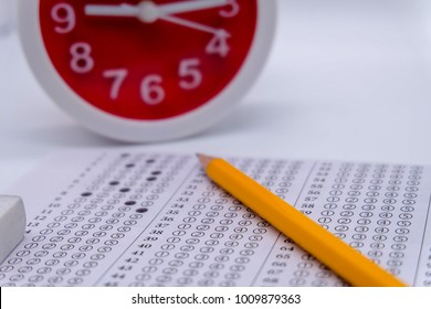 Answers sheet with yellow sharp pencil, clock and rubber isolated on white background, selective focus, blur background. Take the exam timely concept.