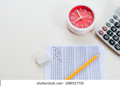 Answers sheet with yellow sharp pencil, clock, calculator and rubber isolated on white background. Top view of them. Take the exam timely concept.
