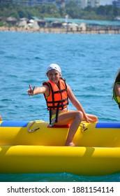 Antalya Turkey 20.08.2020: The Young Girl Sitting On Banana Boat And Enjoying The Summer.