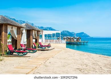 Antalya, Turkey - 8 May 2018: Wooden beach pavilions on the shore of a sandy beach - the Mediterranean coast, Beldibi, Antalya, Turkey