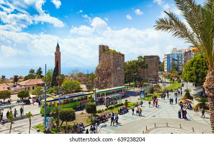 Antalya, Turkey - April 08, 2017: People walking near Clock Tower, Tekeli Mehmet Pasa Mosque and Yivli Minare Mosque or Alaaddin Mosque located in Kaleici district old town center of Antalya, Turkey.