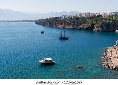 Antalya, Turkey - April 22, 2018: Mountains and Three yatches in the sea. Landscape from Antalya Turkey.