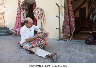 Antalya, Turkey - april 24, 2012: Turkish carpet master repearing old  traditional turkish carpet sitting on the ground  in Old town Kaleici in Antalya, Turkey