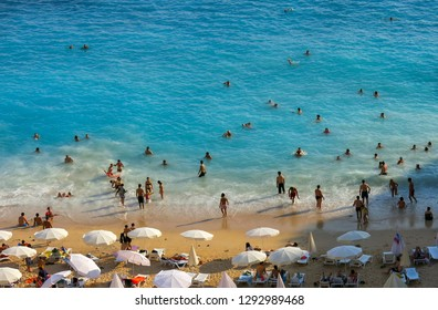 Antalya, Turkey, August 10 2018: Famouse Antalya Kaputas beach, close up photo while a lot of people are inside the wavy turquoise coloured sea and swimming.