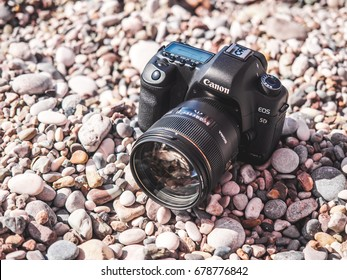 Antalya, Turkey - June 29, 2017: Closeup of Canon 5D mark 2 interchangeable-lens professional dslr camera with Prime Sigma 85mm portrait lens on the beach. Dustproof. Mediterranean sea