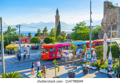 ANTALYA, TURKEY - MAY 11, 2017: The crowded Cumhuriyet street with antique rampart, Yivliminare of Alaaddin Mosque, vintage trams and horse carriages, on May 11 in Antalya.