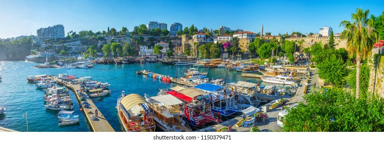 ANTALYA, TURKEY - MAY 11, 2017: Panorama of marina with pleasure boats, medieval ramparts and lush greenery around the promenade, on May 11 in Antalya.