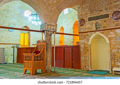 ANTALYA, TURKEY - MAY 12, 2017: Alaaddin Mosque (Yivliminare or Ulu Cami) is decorated with Arabic calligraphy, Roman columns, carved furniture with Islamic patterns, on May 12 in Antalya.