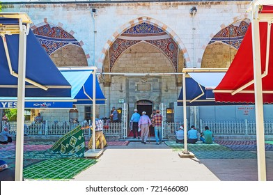 ANTALYA, TURKEY - MAY 13, 2017: Muslims go to Murat Pasha Mosque and prepare for Friday Prayer, street is full of carpets and sunshades for those, who will pray at the street, on May 13 in Antalya.