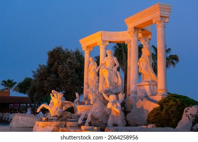 Antalya, Turkey - May, 2021: The symbol of the Alva Donna Exclusive Hotel - statues near the pool in the evening colorful lighting