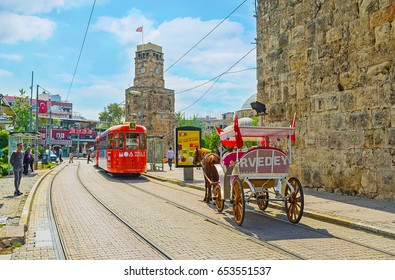ANTALYA, TURKEY - MAY 6, 2017: The trams and horse carriages in Cumhuriyet avenue next to the Clock Tower (Saat Kulesi) and preserved ramparts, on May 6 in Antalya.