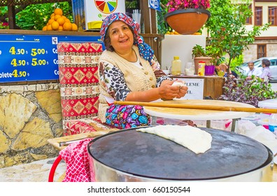 ANTALYA, TURKEY - MAY 6, 2017: The laughing cook makes gozleme - she kneads the dough, while prepared flatbread is heated on griddle, on May 6 in Antalya.
