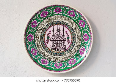 Antalya, Turkey, May 8, 2016: Green plate with oriental ornament hanging on a white stone wall