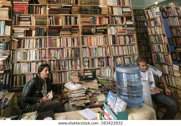 Antalya, Turkey, May 8, 2016:  Many books on a wooden rack and two men sitting in a library