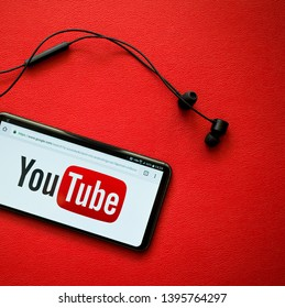 Antalya/Turkey - April 20, 2018: Youtube logo on LG V30 Plus screen with head phones. YouTube is the largest video sharing website in the world. No people in the picture, Red leather background