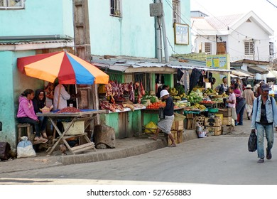 ANTANANARIVO, MADAGASCAR - CIRCA OCTOBER 2016: Sidewalk stalls selling fruit and meat, with the crowd passing in front