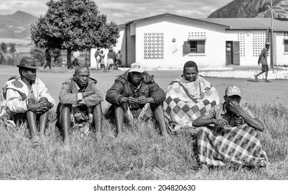 ANTANANARIVO, MADAGASCAR - JULY 1, 2011: Unidentified Madagascar people sit on the grass. People in Madagascar suffer of poverty due to slow development of the country