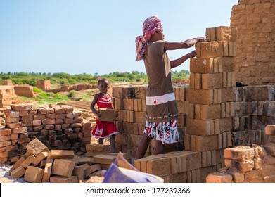 ANTANANARIVO, MADAGASCAR - JULY 3, 2011: Unidentified Madagascar woman makes a wall of bricks and a little girl helps her. People in Madagascar suffer of poverty due to slow development of the country