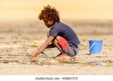 ANTANANARIVO, MADAGASCAR - JULY 3, 2011: Unidentified Madagascar boy plays with sand. People in Madagascar suffer of poverty due to slow development of the country