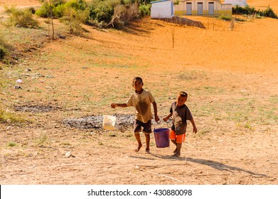 ANTANANARIVO, MADAGASCAR - JULY 3, 2011: Unidentified Madagascar boys bringing water. People in Madagascar suffer of poverty due to slow development of the country