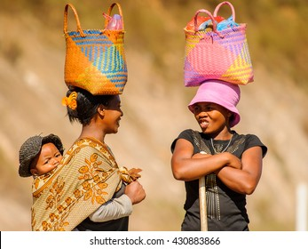 ANTANANARIVO, MADAGASCAR - JUN 27, 2011:Unidentified Madagascar women walk and carry bags on their heads and a baby on a back.People in Madagascar suffer of poverty due slow development of the country