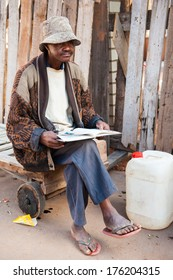 ANTANANARIVO, MADAGASCAR - JUNE 30, 2011: Unidentified Madagascar man reads a book in the street. People in Madagascar suffer of poverty due to slow development of the country