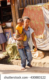 ANTANANARIVO, MADAGASCAR - JUNE 30, 2011: Unidentified Madagascar woman carries her little baby. People in Madagascar suffer of poverty due to slow development of the country