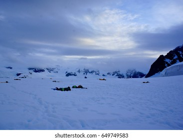 Antarctic camping: the sun dips low on the horizon but never quite sets over intrepid adventure travelers spending a night in the open air.