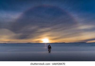 Antarctic Explorer walking towards solar halo