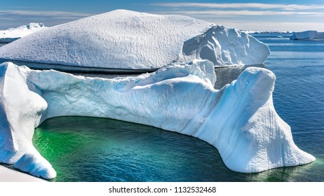 Antarctic iceberg and majestic landscape, sunny day, green lagoon