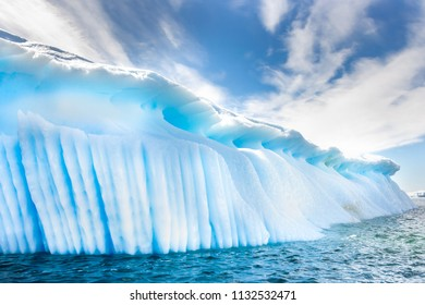 Antarctic iceberg and majestic landscape, sunny day, cloudy blue sky