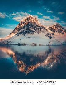 Antarctic landscape with snow covered mountains reflected in ocean water. Sunset warm light on the mountain peak, blue cloudy sky in the background. Exploring beauty world