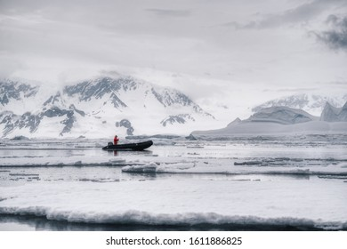 Antarctic Peninsula, Antarctica - January 2019:  A guide on Zodiac boat making way through the floe in Antarctica, among ice, against the rocky shore with glaciers and grey sky