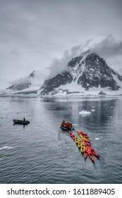 Antarctic Peninsula, Antarctica - January 2019: Group of boats and kayaks in waters near the shores of Antarctica, against picturesque rocky land with low grey clouds