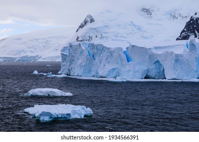 Antarctic scenery with snowy mountains and glaciers and a large blue tabular Antarctic iceberg and smaller icebergs floating off the Errera Channel coast of the Antarctic Peninsula of Antarctica
