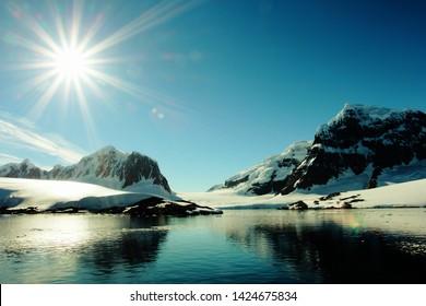Antarctica Antarctic Peninsula Iceberg Icebergs Mountains Lens Flare Sun Lagoon Lake Sunrise Sunshine Sunny Winter Snow Ice Wintry Frozen Cold Icicle Icey Icy Ocean Freezing Snowy Water Reflection