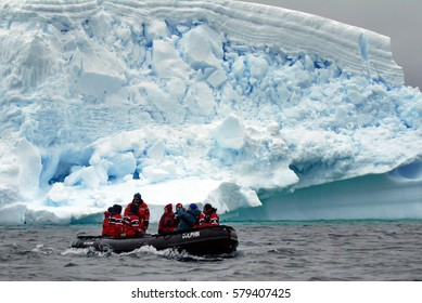 ANTARCTICA - CIRCA JANUARY 2015: Inflatable boat filled with cruise passengers in front of an iceberg