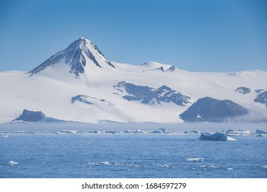 Antarctica peninsula landscape with people, ships, tender boats, penguins, icebergs and mountains