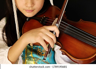 Antelope Valley, CA, USA, August 3, 2020: A young girl dressed in traditional Mongolian dell and headdress, playing a violin