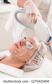 Anti acne phototherapy with professional equipment. Beautiful woman in beauty salon during photo rejuvenation procedure. Laser face skin treatment at cosmetic clinic. Hardware cosmetology