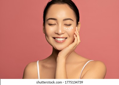Anti aging eye cream. Young Beautiful model posing aginst pink background with applyed cream under her eyes - Shutterstock ID 1775134739