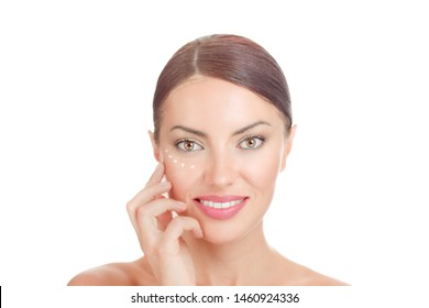 Anti aging eye-cream. Natural brunette model posing hand on cheek, cream around eyes, on face looking at camera isolated on white background. Beauty with flawless skin concept.