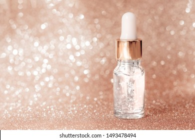 Anti aging serum with collagen and peptides in glass bottle with dropper on golden background. Anti-age product, luxury body care and organic science concept. Dropper glass bottle mock-up.