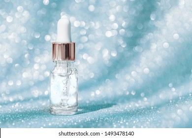 Anti aging serum in glass bottle with dropper on blue shining background. Facial liquid serum with collagen and peptides. Skincare essence for beautiful healthy skin. Dropper glass bottle mock-up.