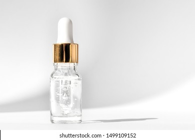 Anti aging serum in glass bottle with dropper on white background. Facial liquid serum with collagen and peptides. Skincare essence for beautiful healthy skin. Dropper glass bottle mock-up.