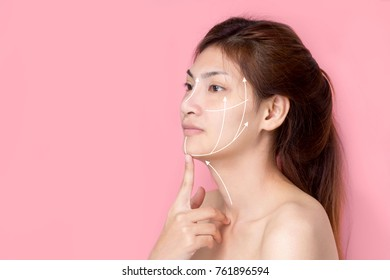 Anti aging treatment and plastic surgery concept. Beautiful young woman with hands on cheeks and eyes closed with a serene expression and white arrows over face.