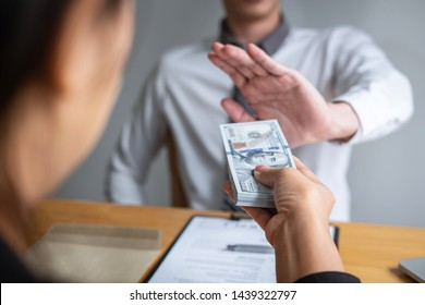 Anti bribery and corruption concept, Business man refusing and don't receive money banknote in envelope offer from business people to accept agreement contract of investment deal.