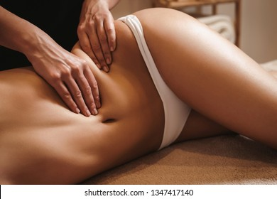 Anti cellulite belly massage for young woman in beauty salon. Perfect skin fat burning beauty concept